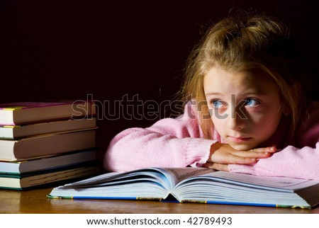 portrait of studying young girl with books on dark background