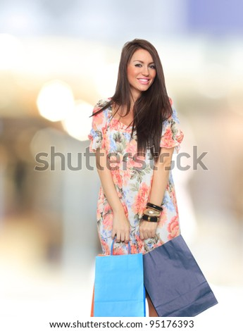 Portrait of stunning young woman carrying shopping bags - stock photo