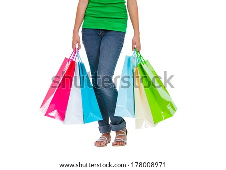 Portrait of stunning young woman carrying shopping bags against white background.