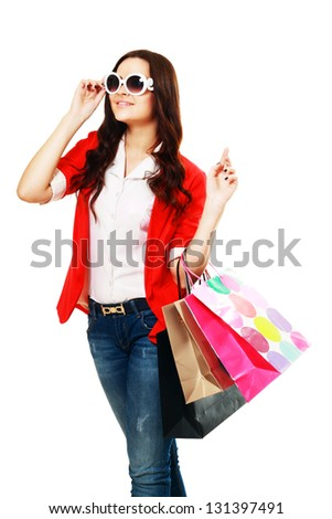 Portrait of stunning young woman in sunglasses carrying shopping bags against white background - stock photo