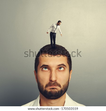portrait of stupid man with small man on the head - stock photo