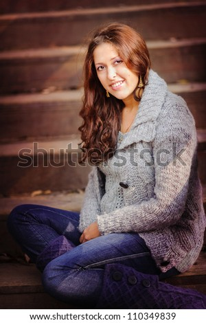 portrait of stylish autumn woman in warm sweater and knitted boots sitting on stairs - stock photo