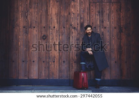Portrait of stylish bearded confident man with vintage suitcase standing on a wooden wall background with copy space for your text message or content,male model with confident look posing outdoors - stock photo