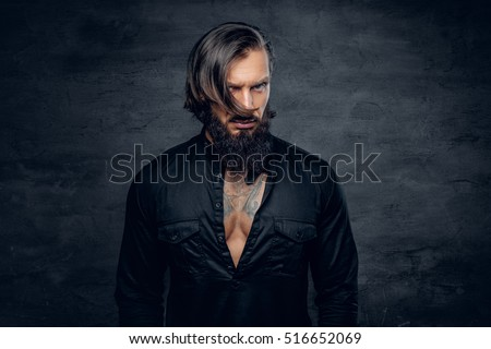 Portrait of stylish bearded man in black glance shirt with tattoo on his chest.