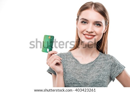 Portrait of stylish beautiful young woman isolated on white background. Woman smiling, looking at camera and holding credit card. Free space for logo - stock photo