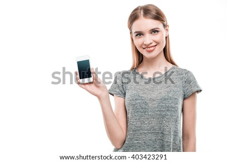 Portrait of stylish beautiful young woman isolated on white background. Woman smiling, looking at camera and showing mobile phone. Free space for logo - stock photo