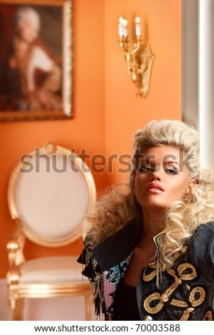 portrait of stylish blond near column in a luxury interior - stock photo