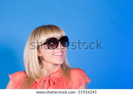 Portrait of stylish casual girl in sunglasses over blue background