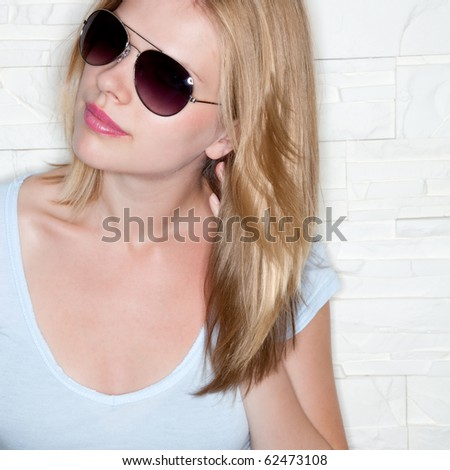 portrait of stylish casual girl with sunglasses in front of a wall - stock photo