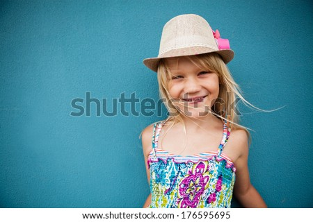 Portrait of stylish cute young girl smiling outside against blue wall background - stock photo