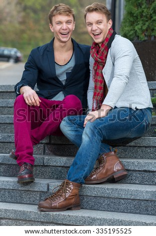 Portrait of stylish fashionable twin brothers sitting on the stairs with cheerful emotions. Twins outdoor fashion style concept.