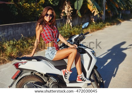 Portrait of stylish girl on scooter - outdoor fashion portrait