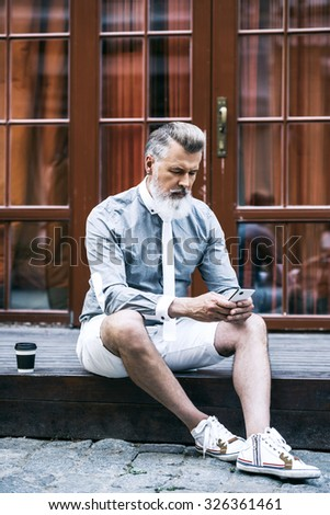 Portrait of stylish handsome adult man with beard sitting outdoors. Man wearing tie and using mobile phone - stock photo