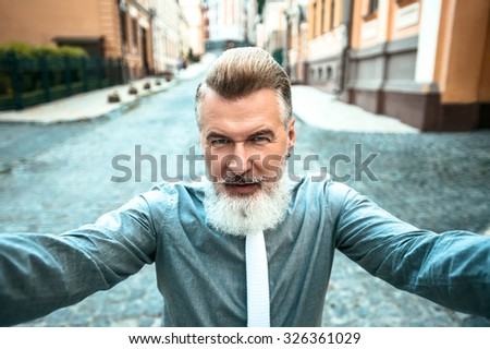 Portrait of stylish handsome adult man with beard standing outdoors. Man staring at camera and holding it with two hands while making selfie photo - stock photo