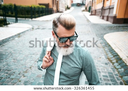 Portrait of stylish handsome adult man with beard standing outdoors. Man wearing glasses and tie - stock photo