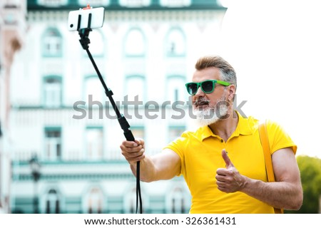 Portrait of stylish handsome adult man with beard standing outdoors. Man wearing glasses and yellow T-shirt, showing thumb up and making photo with selfie stick - stock photo