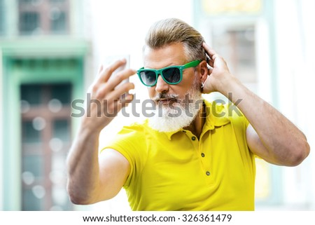 Portrait of stylish handsome adult man with beard standing outdoors. Man wearing glasses and yellow T-shirt, and making selfie photo with mobile phone - stock photo