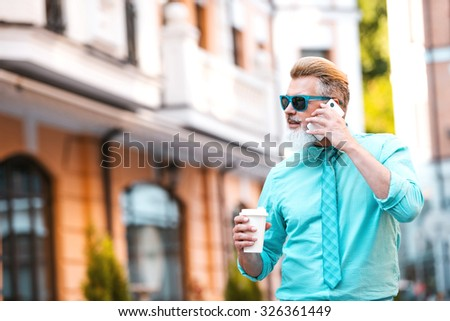 Portrait of stylish handsome adult man with beard standing outdoors. Man wearing glasses, using mobile phone and holding cup of coffee  - stock photo