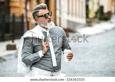 Portrait of stylish handsome adult man with beard standing outdoors. Man wearing tie, holding jacket and cup of coffee - stock photo