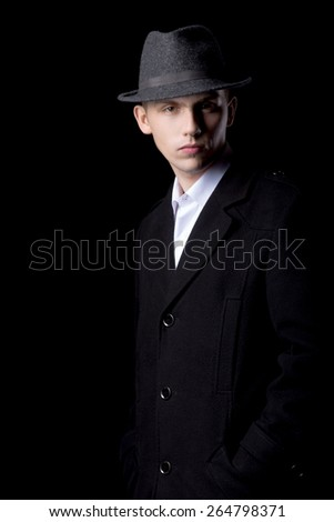 Portrait of stylish handsome confident young man against black background, wearing hat and coat, low key studio shot