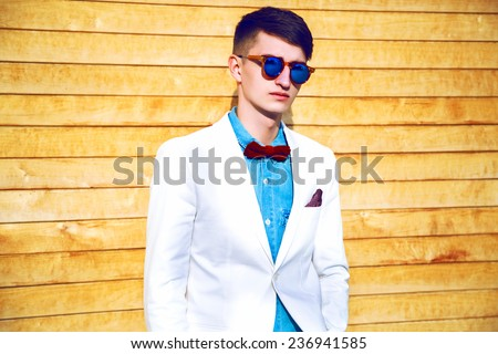 Portrait of stylish handsome hipster guy wearing official trendy suit and bow tie. Man fashion.  Natural wood background, bright sunny colors. - stock photo