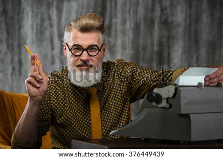 Portrait of stylish handsome writer with beard and glasses. Man wearing shirt, sitting at vintage chair near retro typewriter and holding pencil - stock photo