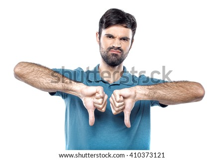 Portrait of stylish handsome young man isolated on white background. Man showing thumbs down and looking at camera - stock photo
