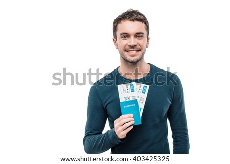 Portrait of stylish handsome young man isolated on white background. Man smiling, looking at camera and holding tickets with passport - stock photo