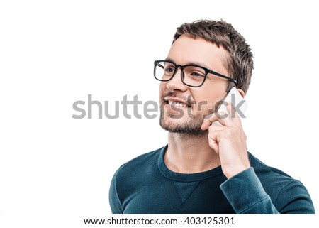Portrait of stylish handsome young man isolated on white background. Man wearing glasses, smiling and using mobile phone - stock photo