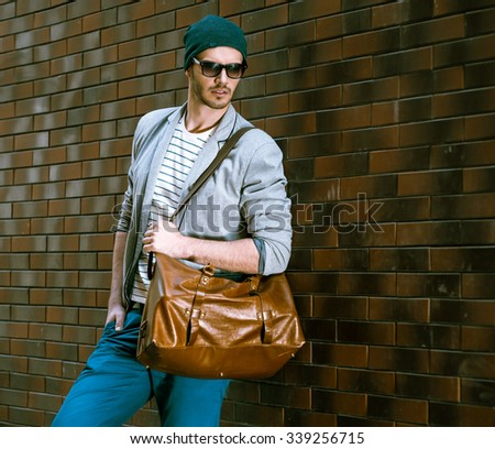 Portrait of stylish handsome young man with bristle standing outdoors and leaning on brick wall. Man wearing jacket and hat. Man with sunglasses holding leather bag - stock photo