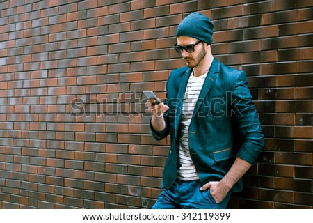 Portrait of stylish handsome young man with bristle standing outdoors and leaning on brick wall. Man wearing jacket and hat. Man with sunglasses using mobile phone - stock photo