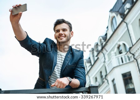 Portrait of stylish handsome young man with bristle standing outdoors. Man wearing jacket and shirt. Smiling man making selfie with mobile phone and leaning on parapet - stock photo
