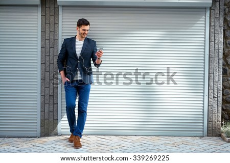Portrait of stylish handsome young man with bristle standing outdoors. Man wearing jacket and shirt. Smiling man listening to music with mobile phone - stock photo
