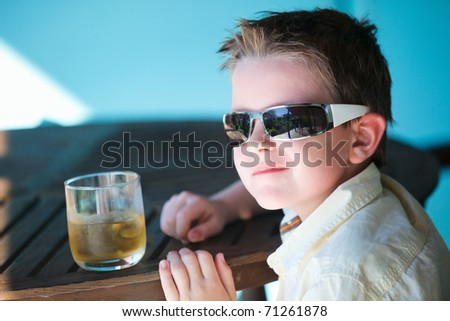Portrait of stylish little boy in sun glasses drinking apple juice