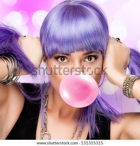 Portrait of stylish party girl with purple wig and bubble gum - stock photo