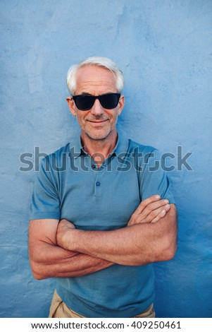 Portrait of stylish senior man with sunglasses standing with his arms crossed against blue background. Handsome middle aged male posing against a blue wall. - stock photo