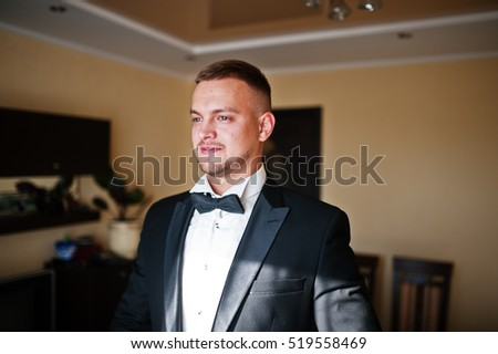 Portrait of stylish young beard man, wearing luxury jacket and bow tie. Gathering of groom on wedding day.
