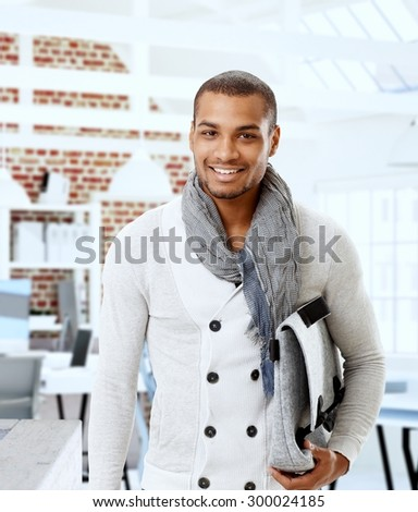 Portrait of stylish young black man holding bag, smiling, looking at camera. - stock photo