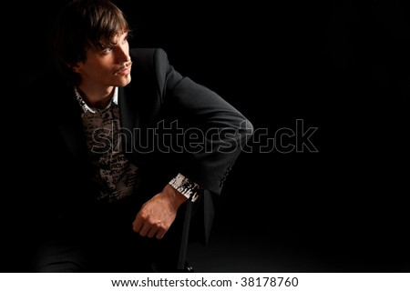 Portrait of stylish young businessman sitting on the flor with black background - stock photo