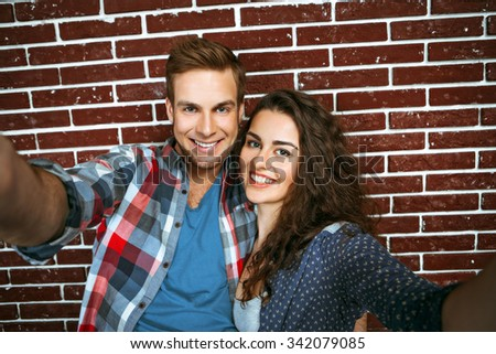 Portrait of stylish young couple standing near brick wall. Woman with curly hair and smiling man making selfie photo - stock photo