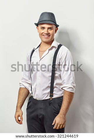 Portrait of stylish young man in suspenders and hat - stock photo