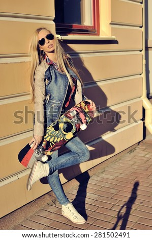 Portrait of stylish young woman in modern clothes in glasses outdoors posing with skateboard