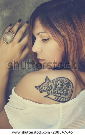 Portrait of stylish young woman with tattoo. - stock photo