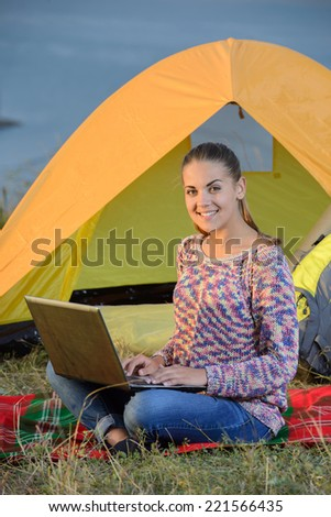 Portrait of succesful woman with laptop sitting in folding chair near camp tent outdoors - stock photo