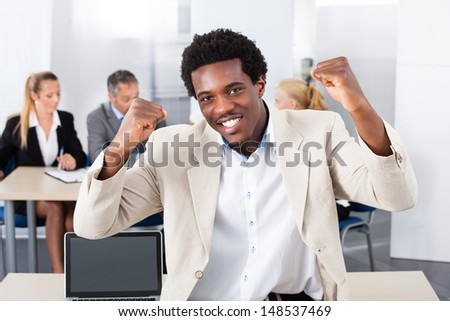 Portrait Of Successful African Businessman Sitting In Front Of Colleagues - stock photo