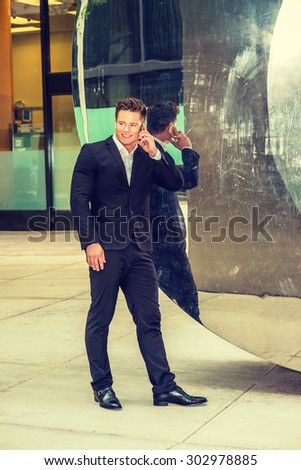 Portrait of Successful American Businessman. Dressing in black suit, leather shoes, a young, strong, sexy guy standing by metal mirror wall, smiling, talking on cell phone. Instagram filtered effect.  - stock photo