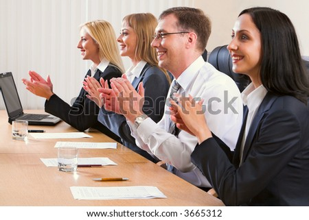 Portrait of successful applauding young people sitting in line in black comfortable chairs at the table with monitor, papers and glasses of water on it - stock photo