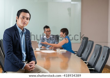 Portrait of successful Asian businessman and his team in background