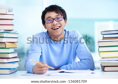 Portrait of successful Asian student sitting at workplace - stock photo