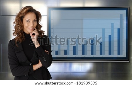 Portrait of successful attractive businesswoman standing by chart of business results, smiling happy front of lcd display.
